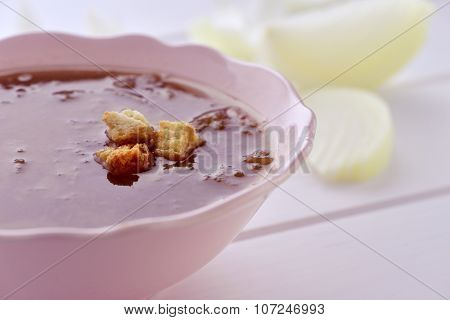 closeup of a bowl with onion soup topped with croutons on a white surface