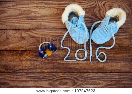 2016 year written laces of children's shoes and a pacifier on the old wooden background. Toned image