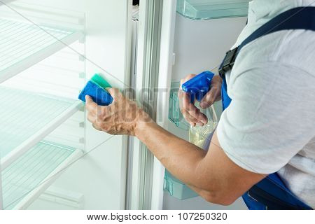 Janitor Cleaning Refrigerator At Home