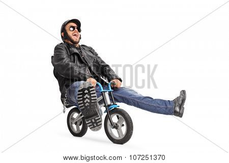 Carefree young biker in black leather jacket riding a small bicycle isolated on white background