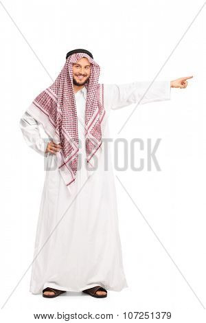 Full length portrait of a young male Arab in a white robe pointing right with his hand isolated on white background