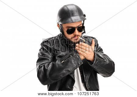 Studio shot of a male biker in a black leather jacket lighting up a cigarette with a lighter isolated on white background