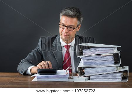 Businessman Checking Invoice With Calculator At Desk