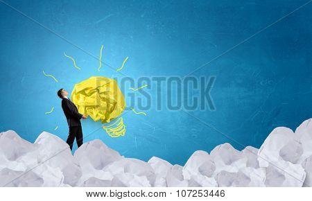 Businessman carrying with effort big crumpled ball of paper as creativity sign
