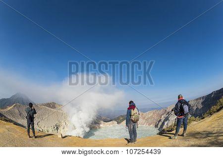 Tourists taking photograph at Kawah Ijen Crater at sunrise panoramic view, Indonesia.
