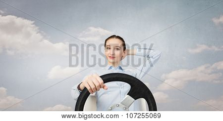 Young smiling pretty woman driving steering wheel