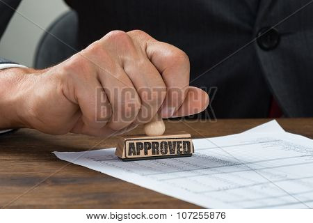 Businessman Stamping Document Marked With Approved