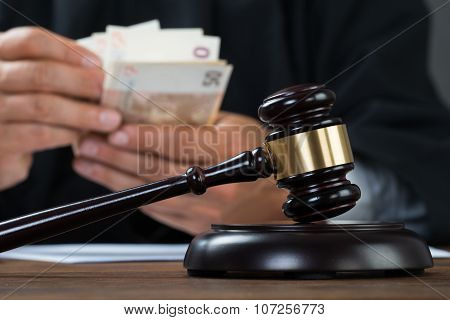 Judge Counting Money At Table