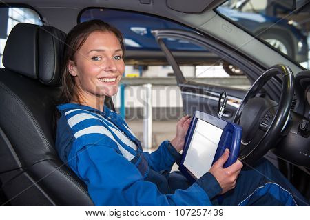 Female mechanic, running a diagnostics program, connected to the computer of the cars, sitting in the drivers seat using a sturdy touch screen terminal