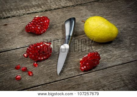 Ripe pomegranates with pear and knife on wooden background.