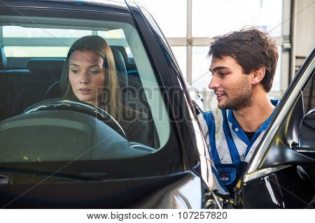 Young woman, behind the wheel of a second hand car, being assisted by a service mechanic, at a used car center