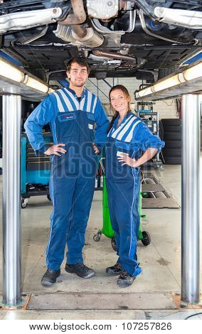 Two smiling mechanics, standing underneath a car on a bridge or car lift, looking confident and professional