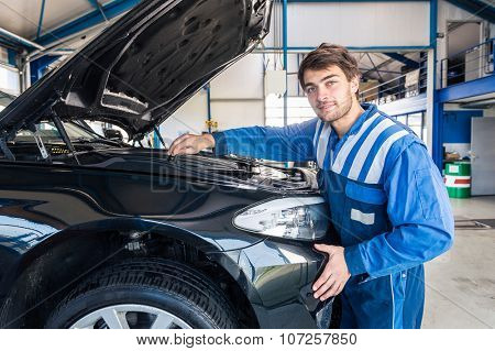 Portrait of a smiling car mechanic looking under the hood of a car