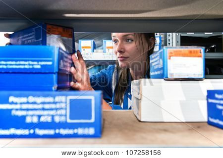 Mechanic picking up spare parts in boxes from a storage rack in a supply room