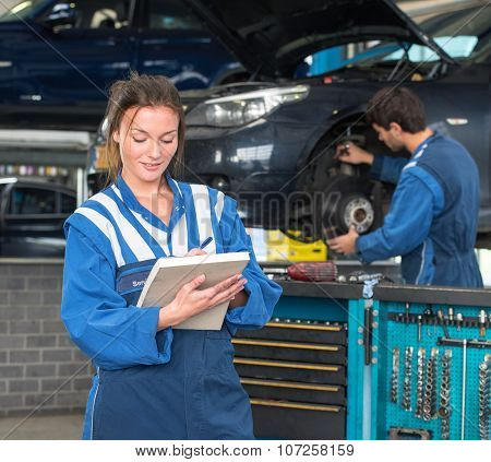 Two mechanics, working in a garage on a MOT test of a car, with a female mechainc in front, checking off inspection items on a  note block, with a tool trolley and her co-worker in the background