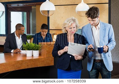 Businesspeople discussing on paperwork while receptionists working at counter in office