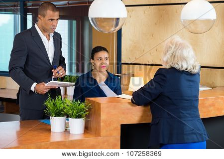 Businesspeople talking to receptionist in modern office
