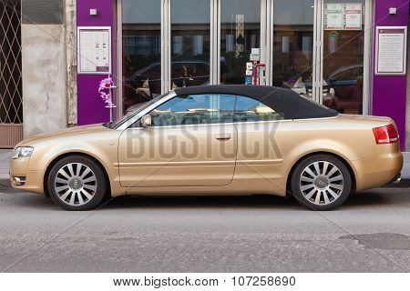 Metallic Gold Audi A4 Cabriolet Stands On City Street