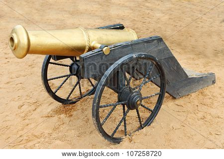 Old Yellow Metal Cannon With Black Wheels On Sand Outdoor At Festival