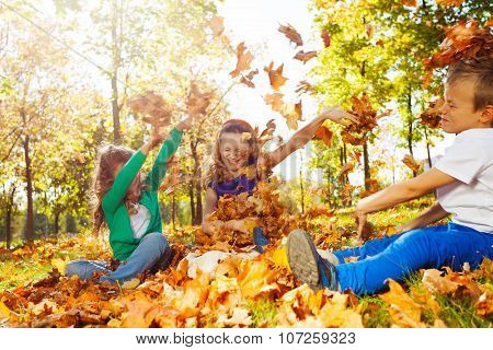 Happy friends having fun with thrown leaves