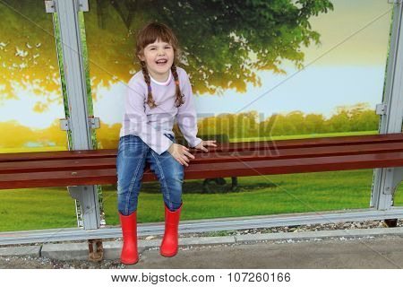 Pretty Girl In Red Gumboots And Jeans Sits On Bench And Laughs