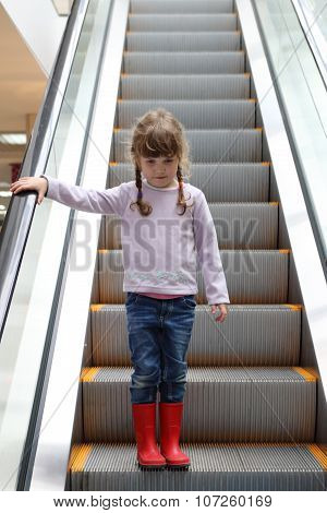 Pretty Girl In Red Gumboots Down On Escalator In Shopping Center
