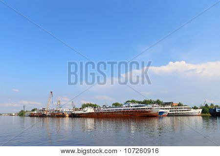 Passengeer Liners, Cargo Ships And Cranes For Loading On River At Summer Day