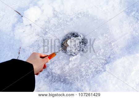 Clean Ice Hole In Frozen Lake For Winter Fishing