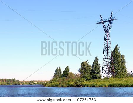 River Coast Line With Green Fresh Grass And Power Transmission Line At Summer Day