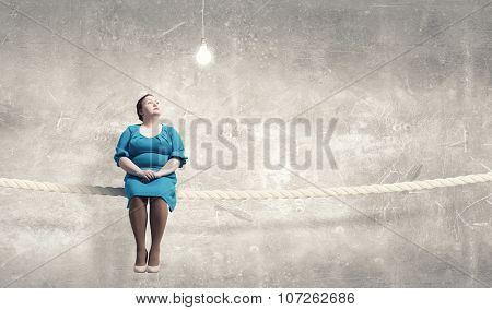 Middle aged stout woman in blue dress sitting on rope