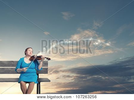 Middle aged stout woman in blue dress sitting on bench and playing violin