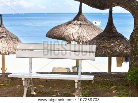 bench for rest under a straw sunshade on the seashore. Mauritius