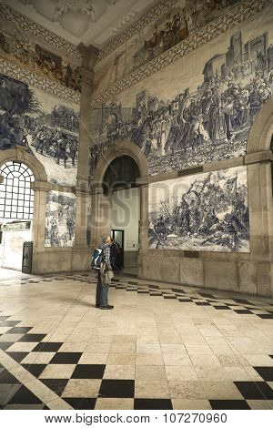 PORTO-PORTUGAL NOVEMBER 3, 2015: Man looking at the fresco into the train station in Porto, Portugal