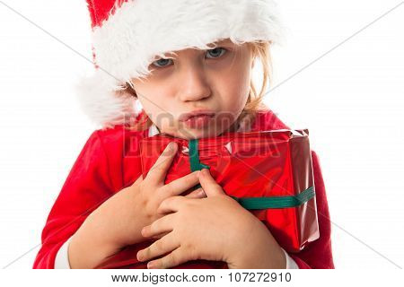 Child In Santa Red Hat Holding Christmas Gifts In Hand. Christmas Concept.