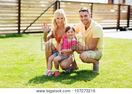 family, happiness, adoption, gesture and people concept - happy family waving hand outdoors