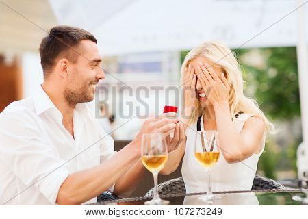 love, proposal, relations, people and holidays concept - happy couple with engagement ring in small red gift box and glasses of wine at restaurant terrace