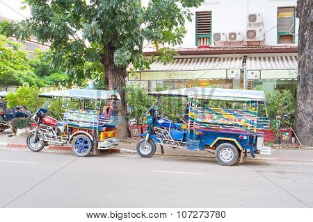 A tuk tuks parked on the side of the main road