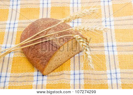 Brown Bread And Three Spikes On A Checkered Tablecloth.