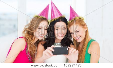 celebration, friends, bachelorette party, birthday concept - three smiling women in pink hats having fun with smartphone photo camera