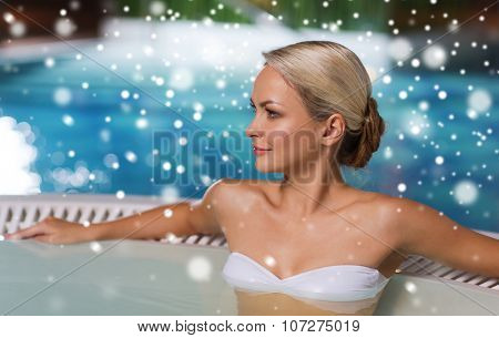people, beauty, spa, healthy lifestyle and relaxation concept - beautiful young woman wearing bikini swimsuit sitting in jacuzzi at poolside with snow effect