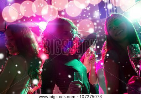 new year party, holidays, celebration, nightlife and people concept - smiling friends with glasses of non-alcoholic champagne dancing at night club and snow effect