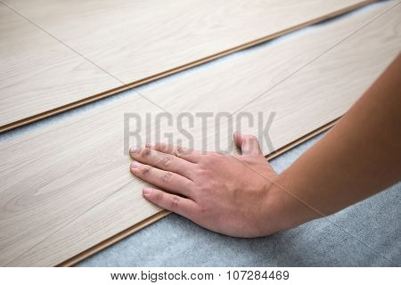 Close Up Of Hands Installing New Laminated Wooden Floor