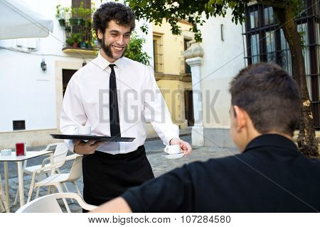 Waiter Serving Coffee On A Terrace