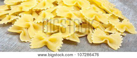 Fine farfalle noodles on wooden board