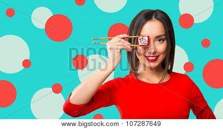 Young Woman Holding Sushi With A Chopsticks, Isolated On Blue