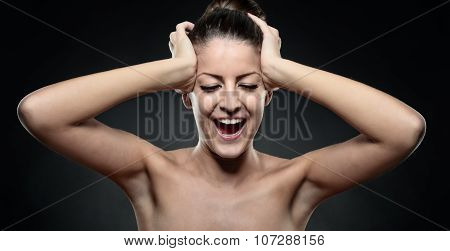Portrait Of Screaming Young Woman With Hands On Head In Black Background