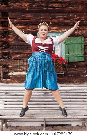 Young woman in Dirndl jumping from a bank