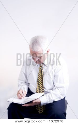 Older Businesman Writing