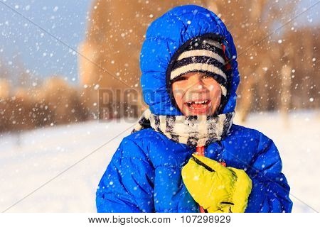 little boy enjoy snow in winter nature