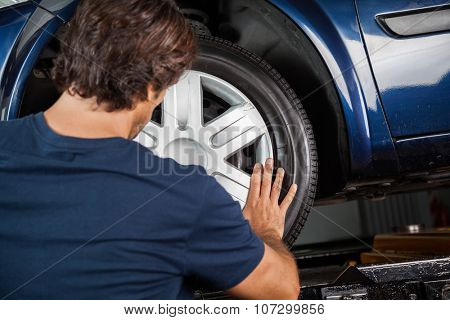 Rear view of male mechanic fixing hubcap to car tire at garage